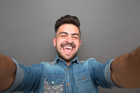 Handsome hipster man opened his mouth because of happiness. Man with fashionable haircut making selfies isolated on grey.
