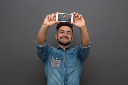 Close-up portrait of handsome hipster man smiling and holding phone in front of him. Man in jeans shirt making selfies isolated on grey. 免版税图像