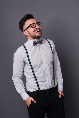 sexy man: Hipster man happy laughing and keeping his hands in pockets. Short-haired man in glasses closed his eyes and smiling in photo studio.