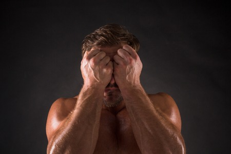 naked male body: Top view of shirtless mascular man closing his face by two wrists. Tanned man posing for photographer over dark grey background.