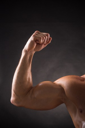 strong arm: Bodybuilder showing his right bicep over dark grey background. Tanned man posing for photographer in studio.
