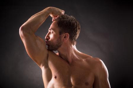 beso: Bodybuilder besando su bíceps sobre fondo gris oscuro. Hombre de pelo corto posando con los ojos cerrados en estudio fotográfico.