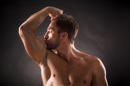 in kiss: Bodybuilder kissing his biceps over dark grey background. Short-haired man posing with his eyes closed in photo studio.