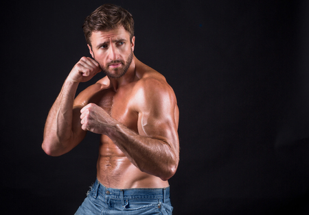 mascular: Serious shirtless mascular man going to fight or to have a battle. Bearded short-haired man in jeans training over dark background. Stock Photo