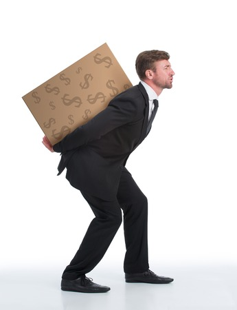 Successful businessman is a real professional in his company. Man in black business suit carrying heavy load with money on his back isolated on white.