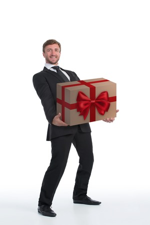 carrying heavy: Smiling businessman carrying heavy present with red bow. Handsome man dreaming to make surprise to his collegues.