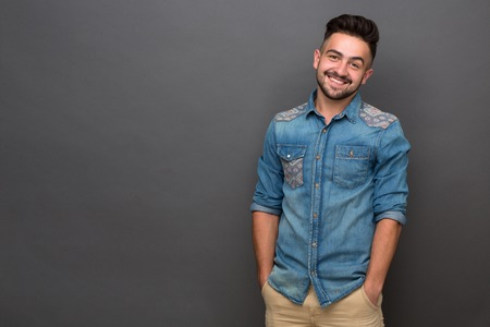 Handsome hipster man posing with his hands in pockets isolated on grey. Man with stylish haitcut smiling for the camera in studio. Stock Photo