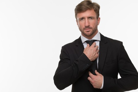 Sexy businessman in black business suit adjusting his tie isolated on white. Handsome man posing in photo studio for photographer. Stock Photo