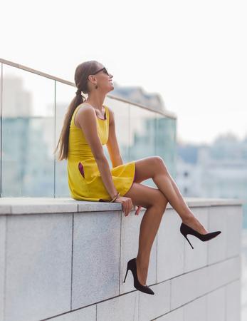 chica de moda en poco vestido amarillo que se sienta en la pared de ladrillo con las piernas cruzadas. Señora bonita en gafas de sol y zapatos de tacón alto mirando a otro lado.