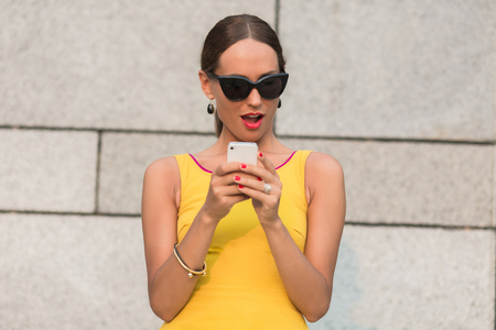 Fashion girl with red lips looking at mobile phone with excitement. Lady in sunglasses in surprised by the information she saw.