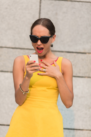 awful: Surprised fashion girl reading awful and disgusting information over mobile phone. Lady in sunglasses posing near office building. Stock Photo