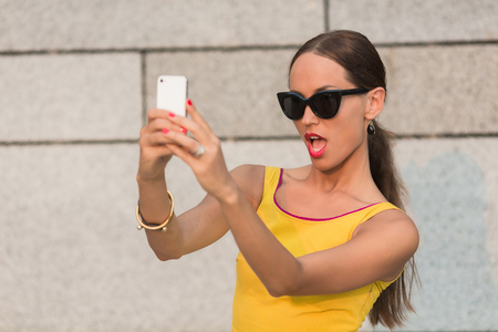 pretty woman face: Fashion girl making selfies vogue photos. Pretty girl with long brown hair looking at the camera. Woman with red lips holding mobile phone in front of her.