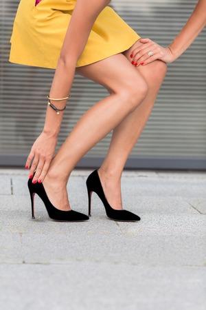 하이힐에 슬림하고 날씬한 여자의 다리의 초상화를 확대합니다. 시내 중심에 작은 노란 드레스 산책 패션 아가씨. 스톡 콘텐츠