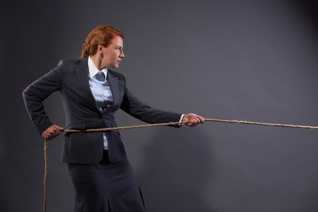 heave: Conceptual image. Businesswoman pulling on a strong rope isolated on dark grey. Lady is not afrait of existing problems.