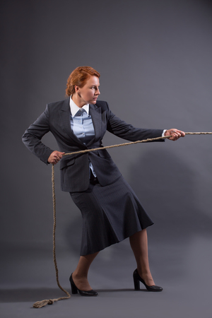 heave: Businesswoman on high heels hauling at a rope from her competitor. Lady in grey business suit dreaming to be a winner.