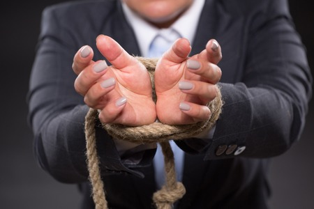 tied up: Close-up picture of female hands tied up with strong rope. Businesswoman ingrey business suit trying to escape from these problems. Stock Photo