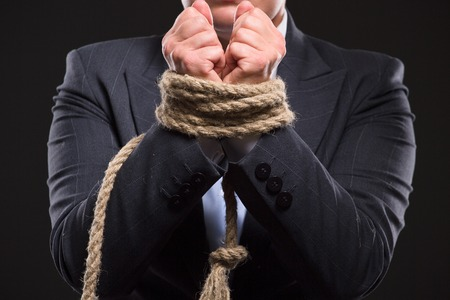 enslaved: Businesswomans hands were tied up with strong rope as if she has serious financial problems. Lady in business suit doesnt know what to do. Stock Photo
