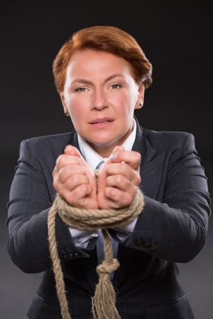 tied up: Portrait of businesswoman demonstrating her hands tied up with strong rope. Serious woman in business suit ready to throw down her arms.