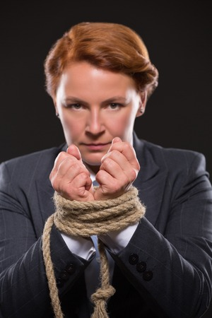 tied up: Portrait of businesswomans hands tied up in rope. Businesswoman with red hair looking at the camera with corageous glance.