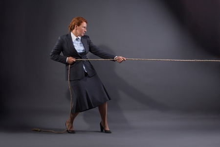 heave: Businesswoman hauling at a rope isolated on dark grey background. Lady in business suit ready to fight for her position. Stock Photo