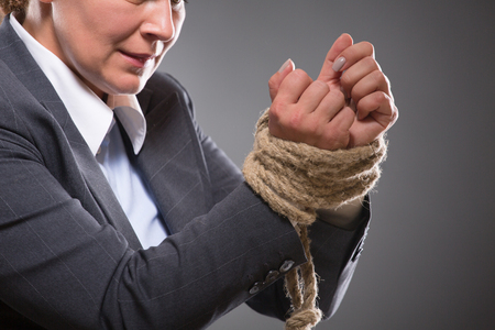 tied up: Close-up picture of tied up hands with strong rope. This businesslady having serious problems in her professional careee. She has to fight to succeed.