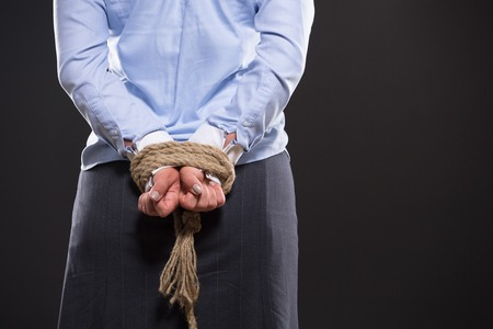tied up: Close up picture of tied up hands with strong rope behind womans back. Lady in blue shirt is connected with business system.