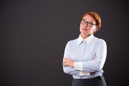 businesslady: Professional and business concepts. Smiling businesslady in glasses keeping her arms crossed isolated on dark grey background. Stock Photo