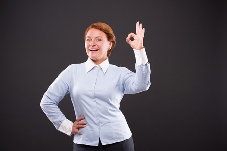okay: Smiling businesslady showing okay sign and keeping one hand on hip. Happy woman in blue shirt knows exactly that everything will be okay. Stock Photo