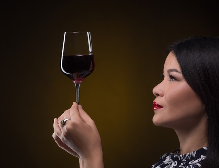 sommelier: Close-up pictire of glass of expensive red wine. Professional sommelier woman studying new type of red wine. She is going to taste it. Stock Photo
