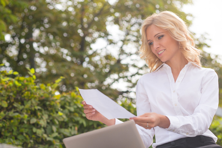 oudoors: Freelance and business concepts. Lady working with her laptop oudoors. Beautiful woman with blond hair holding a sheet of paper in her hands.