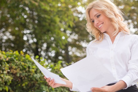 oudoors: Freelance lady looking at her documents and smiling. Pretty blond woman in white shirt working oudoors in the nature.