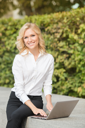 oudoors: Freelance lady working with laptop computer and smiling for the camera oudoors. Blonde in white shirt and black trousers sitting on brick wall.