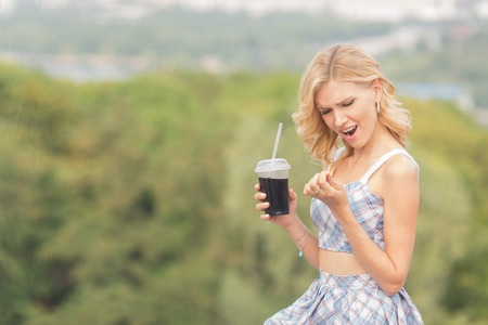 Young girl drinking cocktail outdoors and loong at her nails with amazement. Pretty lady is not satisfied with her manicure.