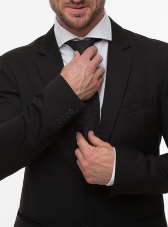 Close-up image of businessman adjusting his expensive tie isolated on white. Handsome man in black business suit in studio.