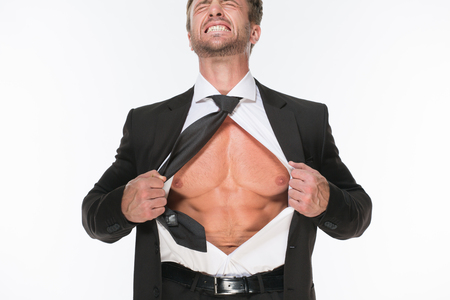 striping: Businessman showing his chest and clenching his teeth isolated on white background. Sexy man holding his shirt and posing for photographer. Stock Photo