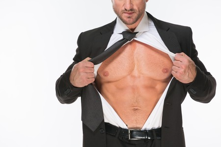 undress: Close-up image of businessmans strong chest. Sexy man in black business suit hoding his shirt with two corageous hands.