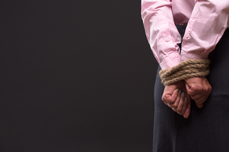 tied up: Profile of womans tied up hands with strong rope. Lady in pink shirt keeping hands behing her back. She is thinking about way out.