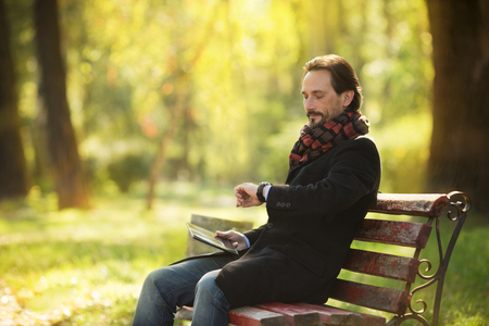 middleaged: Handsome middle-aged man resting on the bench outdoors. Man holding tablet PC and looking at his watch, because he is waiting for someone.