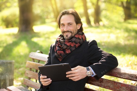 middleaged: Handsome middle-aged man looking at the camera while resting on the bench in the park. Smiling man holding table PC in front of him.