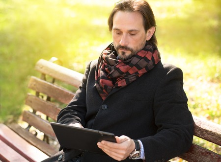 middle aged men: Serious middle-aged man looking at his tablet PCs screen. Man in black coat and with scarf on working on the bench outdoors.