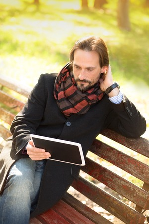 pcs: Handsome middle-aged man looking at table PCs screen and touching his nape while sitting on the bench in the park.
