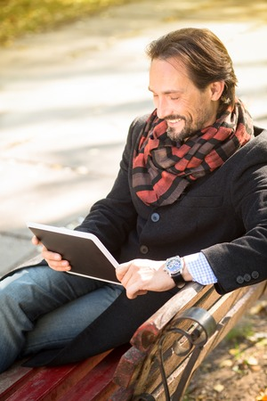 middleaged: Portrait of smiling middle-aged man in black coat working in the park. Handsome man using his tablet PC while resting on the bench outdoors.