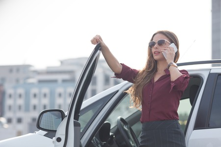 lady on phone: Businesswoman getting out from her car and speaking over mobile phone. Pretty lady in sunglasses touching cars door.