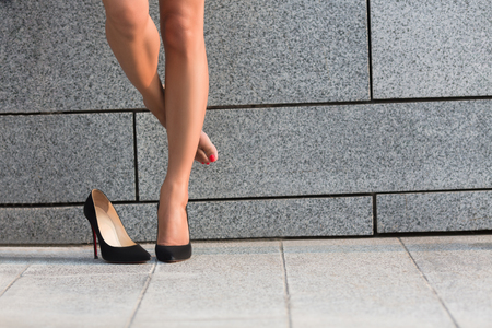 Woman put off right leg from her heel. Beautiful lady hiding right leg behinf left one isolated on brick wall backround. Stock Photo