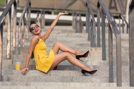 lady: Toothy laughing fashion girl sitting on stairs of office building with orange cocktail. Lady with red lips raising hand to the sky.