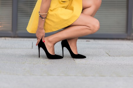 heel: Close-up portrait of womans legs on high heels. Lady in yellow dress sitting and touching her right leg near office building.