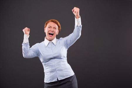 businesslady: Businesslady demonstrating her desire to be the winner. Woman in blue shirt raised two hands and screaming isolated on dark grey background.