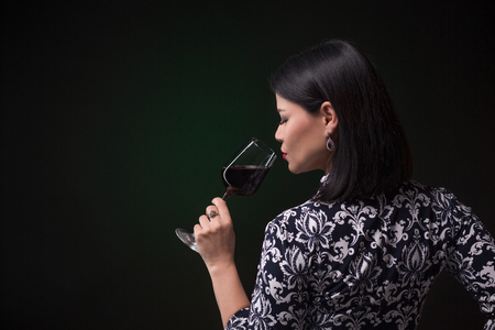 Beautiful asian woman drinking red wine. Back view of middle-aged lady in traditional dress holding a glass of wine in front of her red lips.