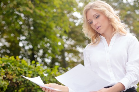 oudoors: Serious freelance lady reading the documents. Blonde likes working oudoors in the park. It is nice time to concentrate. Stock Photo