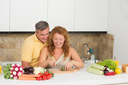 free dish: Happy middle-aged couple preparing dish for lunch in the kitchen. People spending their free time. Red-haired woman chopping vegetables.